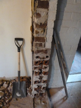 Here you can clearly see that the exterior walls are composed of three layers of brick with plaster on the interior. This wall was covered with drywall at some point.